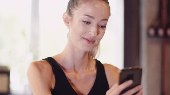 Thumbnail for Junge Frau mit Smartphone im Fitnessstudio