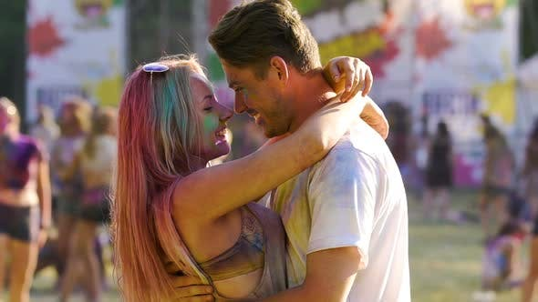 Thumbnail for Young Sweethearts Hugging and Dancing Together at Holi Color Festival Outdoors