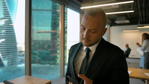 Attractive Handsome Boss in Office Openspace Typing and Chatting with His Deal Partner