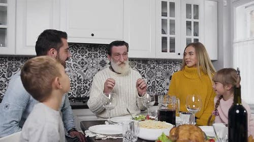 Family of Man, Woman and Their Children with Respected Grandfather Sitting at the Thanksgiving Table