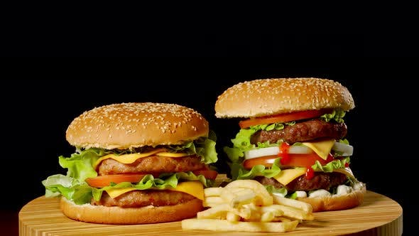 Thumbnail for Two Craft Beef Burgers on Wooden Table Isolated on Dark Grayscale Background.