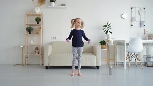 Cute Little Girl Exercising with Dumbbells