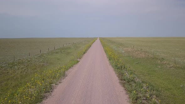 Aerial of Dirt Country Road in Grassland Prairie Landscape Wyoming in Summer