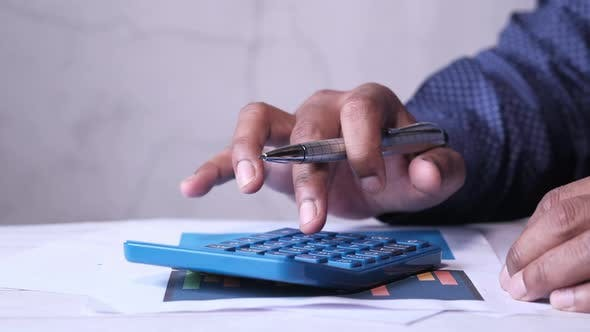 Thumbnail for Close Up of Man Hand Using Calculator on Office Desk