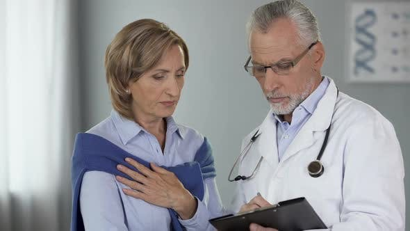 Cover Image for Elderly Doctor Talking to Female Patient Showing Results, Disease, Treatment Way
