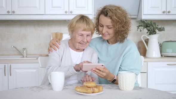 Thumbnail for Family, Generation, Technology And People Concept - Granddaughter And Grandmother With Smartphone