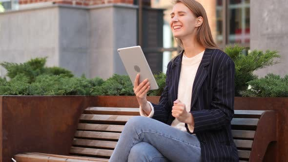 Thumbnail for Woman Sitting on Bench Celebrating Success of Project on Tablet