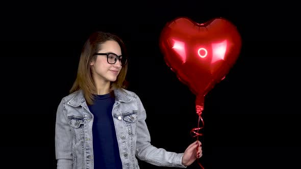 A Young Woman Kisses an Inflatable Balloon in the Form of a Heart, Woman with a Balloon Filled with