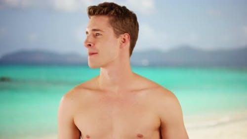 Attractive young millennial Caucasian male staring at beach horizon.  Happy adult man enjoying Carib