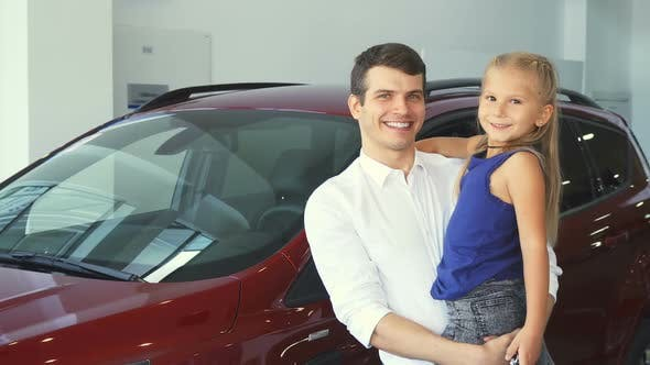 Thumbnail for Dad and Daughter on His Hands Stand on the Background of the Car