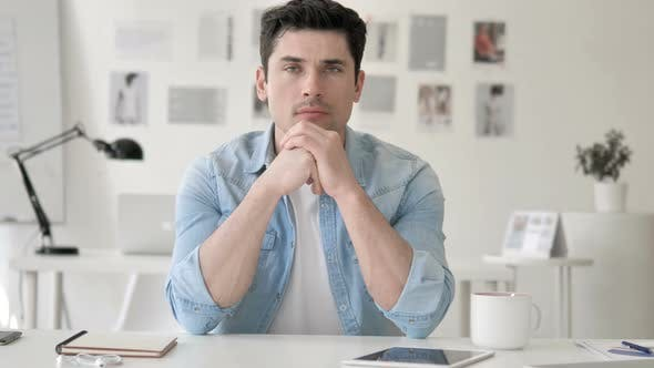 Thumbnail for Confident Casual Young Man Sitting at Workplace