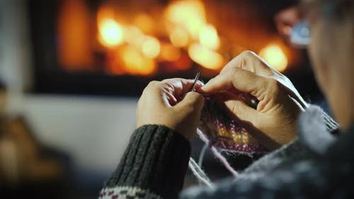 Close-up of the Hands of an Elderly Woman Who Knits a Dull Thing on the Background of the Fireplace