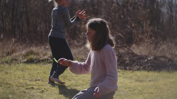 Girl Blowing Bubbles From Plastic Bubble Wand In Sunlit Field
