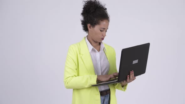 Thumbnail for Happy Young Beautiful African Businesswoman Thinking While Using Laptop