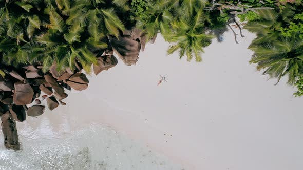 Thumbnail for Aerial View Vertical Move Up Footage From Girl Laying on a White Sand Beach Surrounded By Crystal