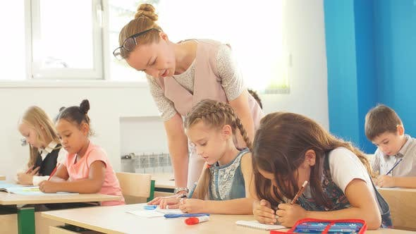 Thumbnail for Teacher Helping Kids with Their Homework in Classroom at School