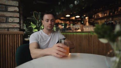 Man Drinks Fruity Juice in Restaurant Looking Into Smartphone