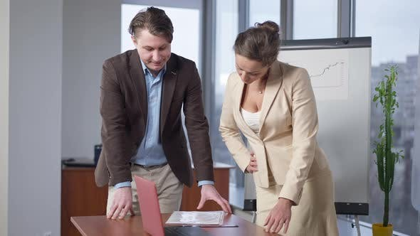 Handsome Man and Beautiful Woman Discussing Document in Office