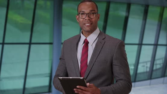Thumbnail for Proud African-American corporate employee using pad in business building lobby