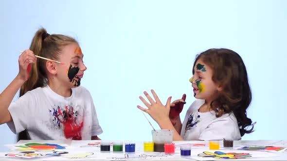 Thumbnail for Kid Sitting at the Table Applying Paints To Their Clothes. White Background. Slow Motion