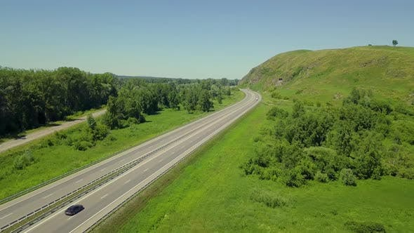 Thumbnail for Aerial: Low Level Flying Over Highway in the Highlands. View of the Forest, Passing Cars, Trucks