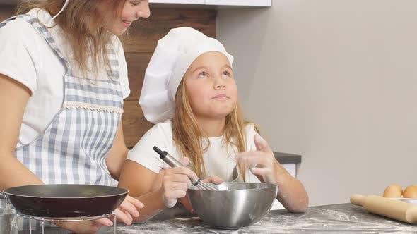Junge Köche sind in der Zubereitung von Kuchen beschäftigt, Litlle Girl schmeckt den Teig