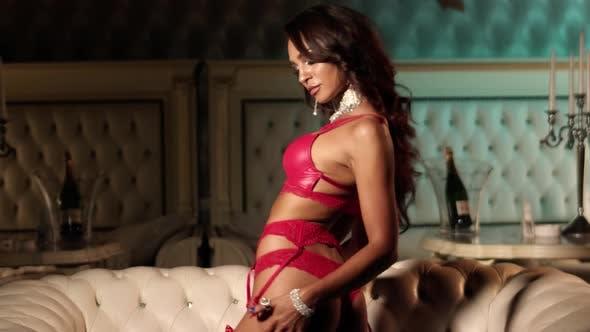 Sexy Frau mit perfektem Körper tanzt und berührt ihren Körper in roten Dessous.