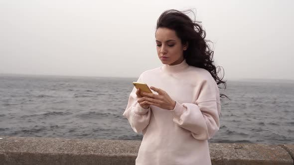 Woman is standing near the sea and looking at her cell phone