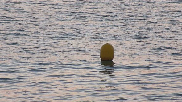 Yellow Buoy Bobs on the Waves
