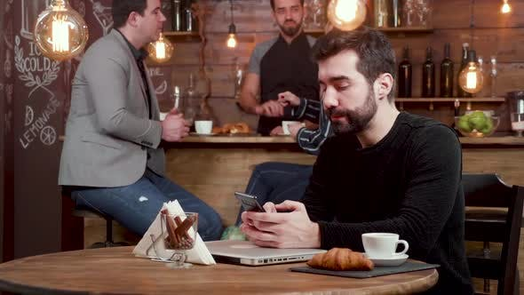 Thumbnail for A Young Man Texting on His Smartphone, Grabs His Laptop and Leaves the Coffe Shop