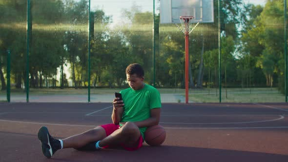 Thumbnail for Basketball Player with Phone Relaxing on Outdoor Court