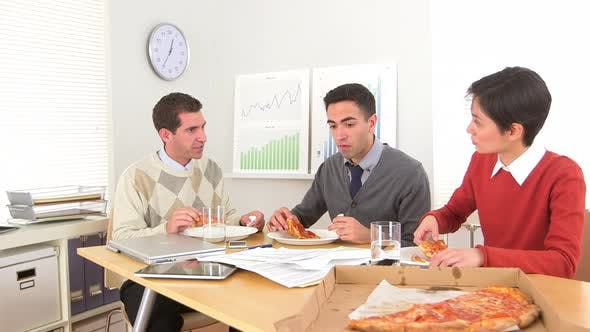 Thumbnail for Businessteam eating pizza while at work