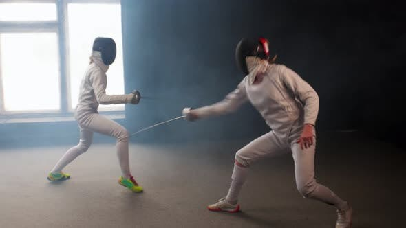 Cover Image for Two Young Women Having an Intense Training in a Fencing Duel in the Smoky Studio