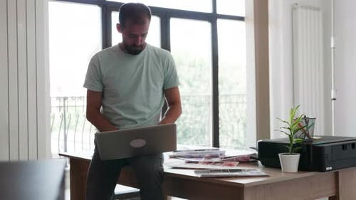 Young Fashion Desginer Wokring on His Computer in His Modern Office