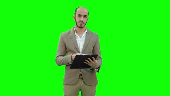 Cover Image for Businessman Holding Clipboard and Presenting Business Report on a Green Screen