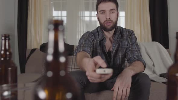 Thumbnail for Young Bearded Man Sitting on the Sofa Takes Remote and Turned on the TV