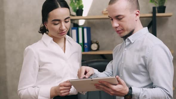 Man and Woman Look at Screen of Tablet and Lead Discussion
