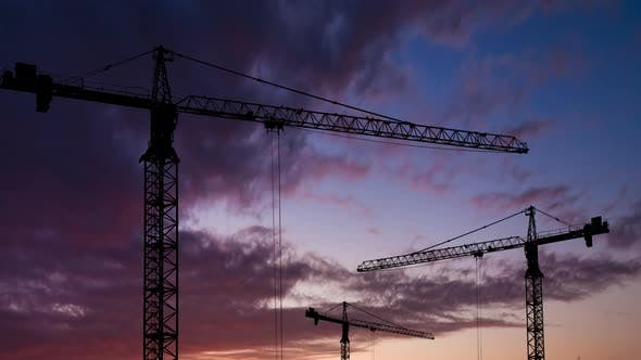Silhouettes of Construction Cranes on the Background of a Beautiful Sunset Sky