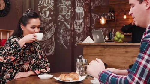 Gorgeous Couple Drinking Coffee and Eating Croissants in Stylish Hipster Coffee Shop Pub Restaurant