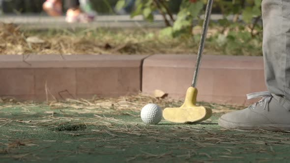 Little Player Beats A Golf Ball To Hole Course