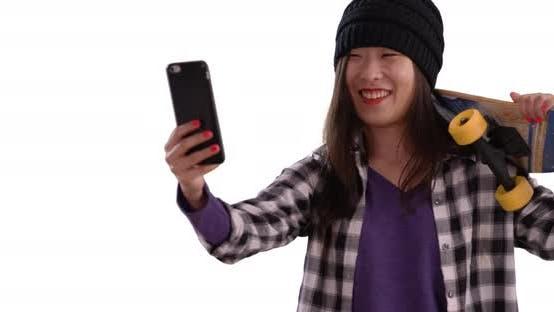 Thumbnail for Lovely millennial skater using technology to take selfie on white background