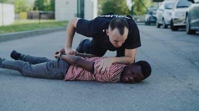Policeman Interrogating Black Man on Ground