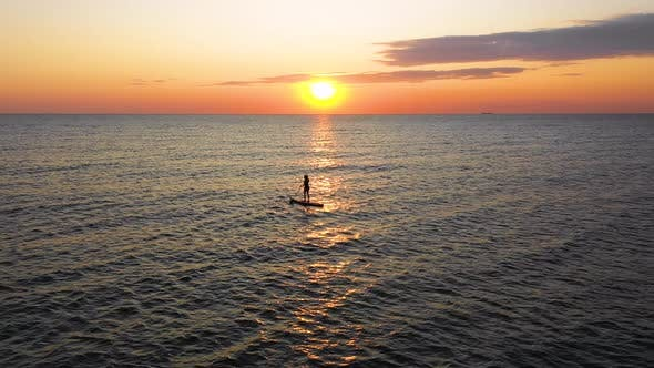 Thumbnail for Young woman on a stand up paddle board exercising at sunset. Girl Silhouette on Water.