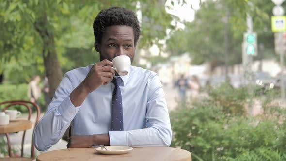 Thumbnail for African Businessman Drinking Coffee while Sitting in Outdoor Cafe