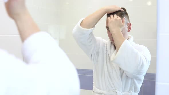 A Young Man Applies Mousse for Laying on the Hair. A Man in a White Bathrobe in Front of a Bathroom