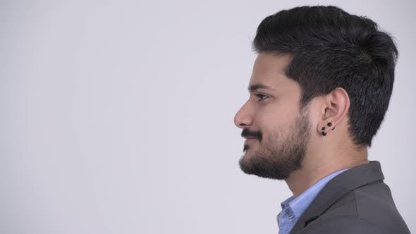 Thumbnail for Profile View of Young Happy Bearded Indian Businessman Smiling