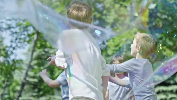 Thumbnail for Kids Catching Bubbles in Park