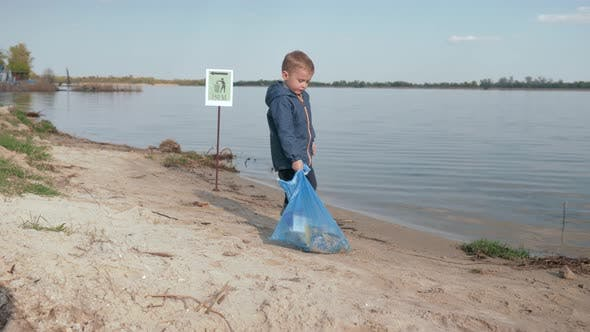 Thumbnail for Stop Pollution, Cute Boy Pulls Heavy Bag of Trash on Pointing Sign on River Beach After Cleaning Up