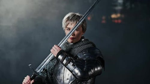 Dramatic Shot of a Woman in a Metal Medieval Warrior Armour with a Sword Examining the Blade While