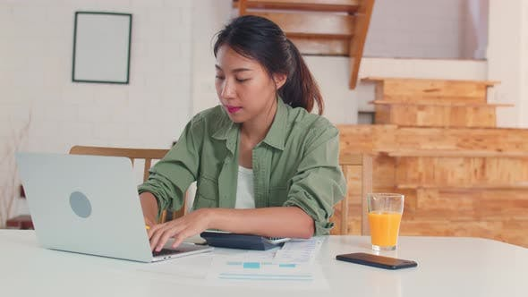 Business Asian women records of income and expenses at home.